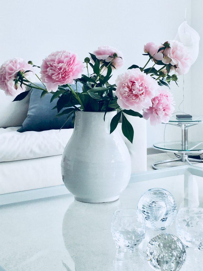 vaaleanpunaisia pioneja vaaleassa maljakossa lasipöydän päällä